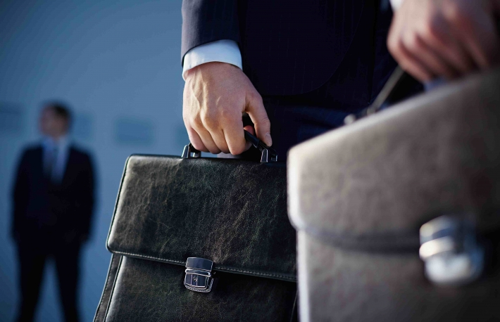 http://www.shutterstock.com/pic-178332941/stock-photo-cropped-image-of-business-partners-carrying-briefcases-on-the-foreground-while-their-colleague.html?src=0rabsJv8P-n-K7N9qFIOrA-1-12
