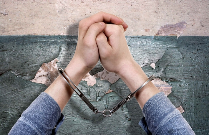http://www.shutterstock.com/pic-265054127/stock-photo-handcuffs-on-hands-on-the-old-wall-background-closeup.html?src=yLBfvfOIkjCEd2RfsZG6rg-1-0