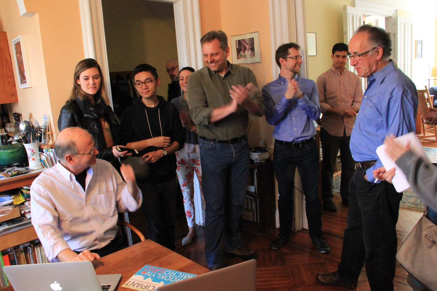 LO3 co-founder, Lawrence Orsini, center, applauds on Monday, April 11, 2016 as Bob Sauchelli, far left, using Transactive Grid technology to buy green energy credits from Eric Frumin.