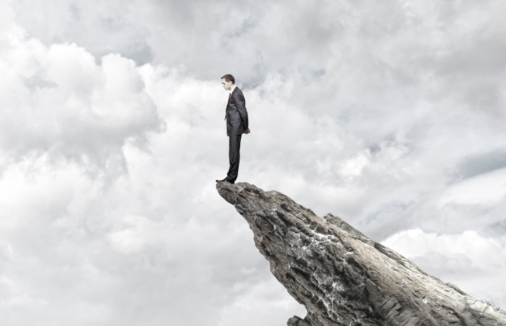 http://www.shutterstock.com/pic-224074003/stock-photo-young-businessman-standing-on-edge-of-rock-mountain.html?src=kzrn8yJwAWlicSIA6ykJjQ-1-8