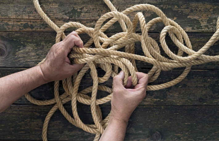 http://www.shutterstock.com/pic-303675002/stock-photo-two-hands-trying-to-untangle-a-rope-wooden-background.html?src=h2Au-6s__CNCFdi26xtLoQ-1-32