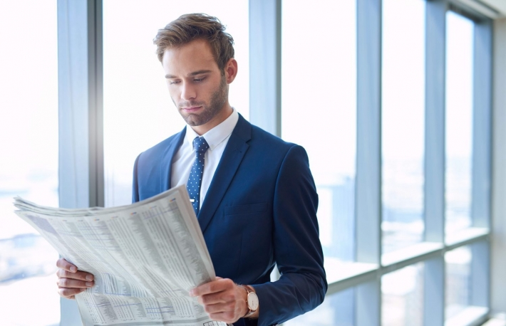 http://www.shutterstock.com/pic-433548139/stock-photo-young-financial-executive-standing-alongside-large-windows-reading-a-newspaper-and-gaining-insight.html