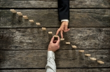 http://www.shutterstock.com/pic-326943551/stock-photo-conceptual-image-of-business-partnership-and-support-businessman-supporting-wooden-step-in-a-staircase-made-of-pegs-as-his-partner-walks-his-fingers-up-towards-growth-achievement-and-de.html?src=yxSZTPznS8r19i1-6j9EnA-1-61
