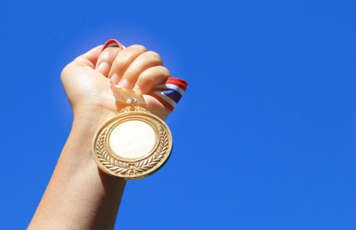 http://www.shutterstock.com/pic-515388625/stock-photo-hand-raised-and-holding-gold-medal-against-blue-sky-award-concept.html