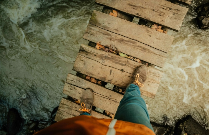 http://www.shutterstock.com/pic-371905453/stock-photo-mans-legs-on-an-old-wooden-bridge-through-the-river.html