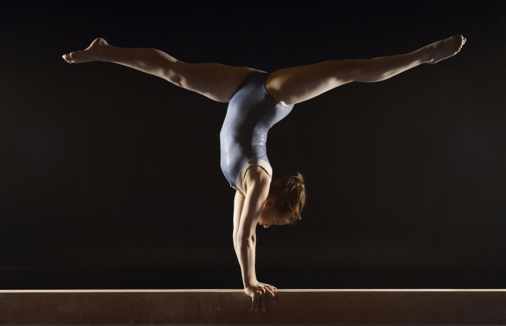 http://www.shutterstock.com/pic-144637058/stock-photo-side-view-of-a-female-gymnast-doing-split-handstand-on-balance-beam-against-black-background.html
