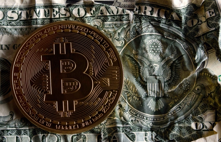 https://www.shutterstock.com/image-photo/bitcoin-on-crushed-dollar-banknote-against-707360806