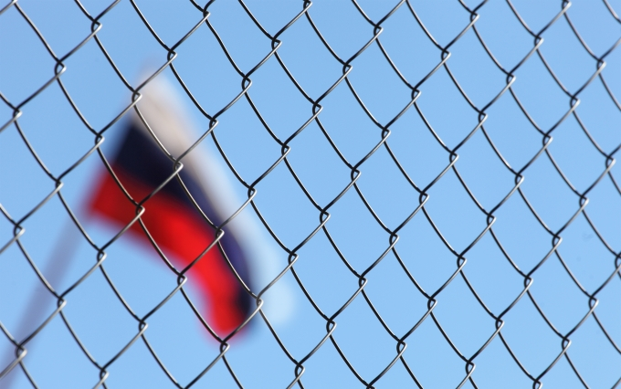 Russian flag behind fence (sanctions)
