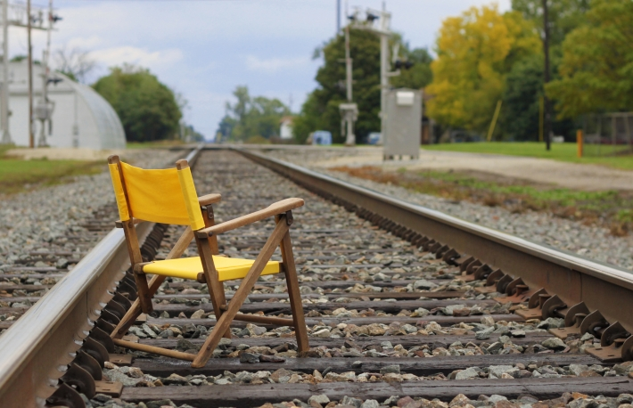 Yellow chair on train tracks, tempting fate