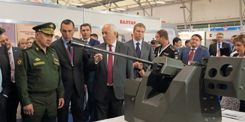 Rostec's CEO Sergey Chemesov shows a model of a tank to Russia's Minister of Defence Sergey Shoygu