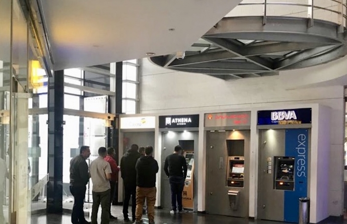 Image of line at bitcoin ATM beside ignored bank ATMs in Bogota, Colombia via Athena Bitcoin
