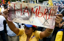 opposition-supporter-holds-up-a-giant-hundred-bolivares-note-with-the-word-hungry-written-on-it-during-a-gathering-to-protest-against-the-government-of-venezuelas-president-nicolas-maduro-and