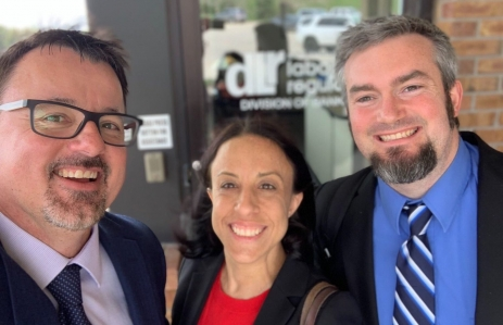 Anchorage Trust Officer Jim Benham, General Counsel Katie Biber and CEO Nathan McCauley pose in front ofthe South Dakota Division of Banking. Photo via Anchorage