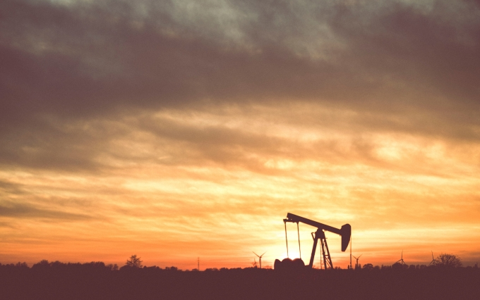 Silhouette of oil derrick during sunset