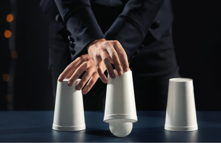 https://www.shutterstock.com/image-photo/magician-showing-tricks-cups-on-dark-1183959967