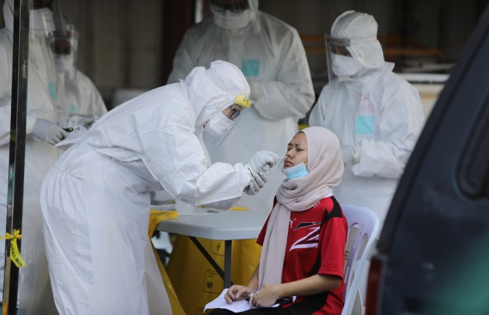 A health worker conducted a COVID-19 coronavirus screening test for residents during a following cases an infections in the area of Kampung Baru in Kuala Lumpur on 12, April 2020