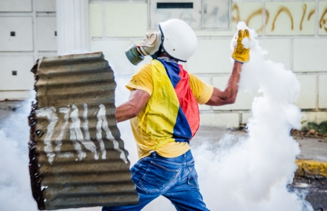 person holding metal shield and tear gas in venezuela