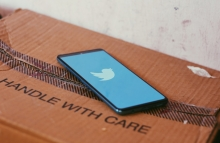 "Phone with Twitter logo on a box that says ""Handle with care"""