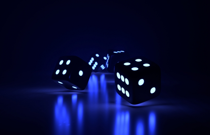 Risk, gambling, bet, wager  Four glowing black dice emitting blue lights rolling on the table