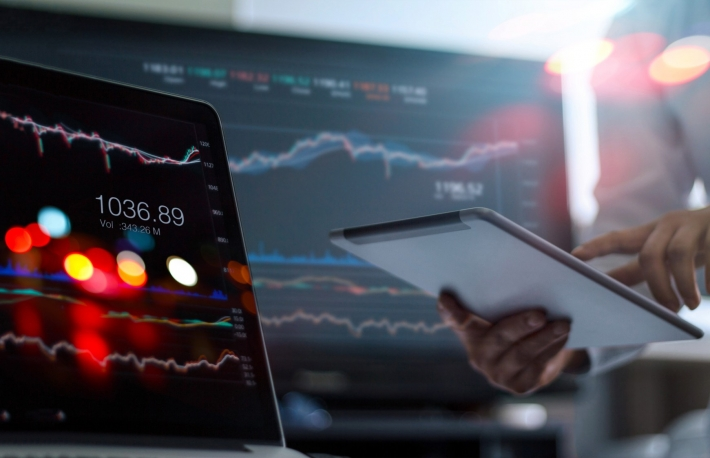 man holds tablet with stock market info